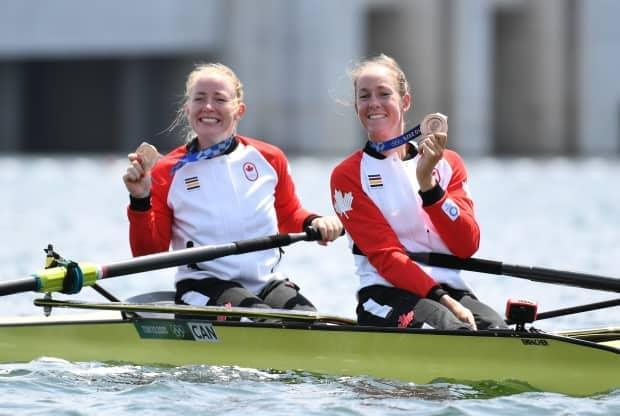 Canadian rowers Caileigh Filmer, left, and Hillary Janssens hold up their bronze medals after reaching the podium in the women's pair final on Thursday at the Tokyo Olympics. (Piroschka Van De Wouw/Reuters - image credit)
