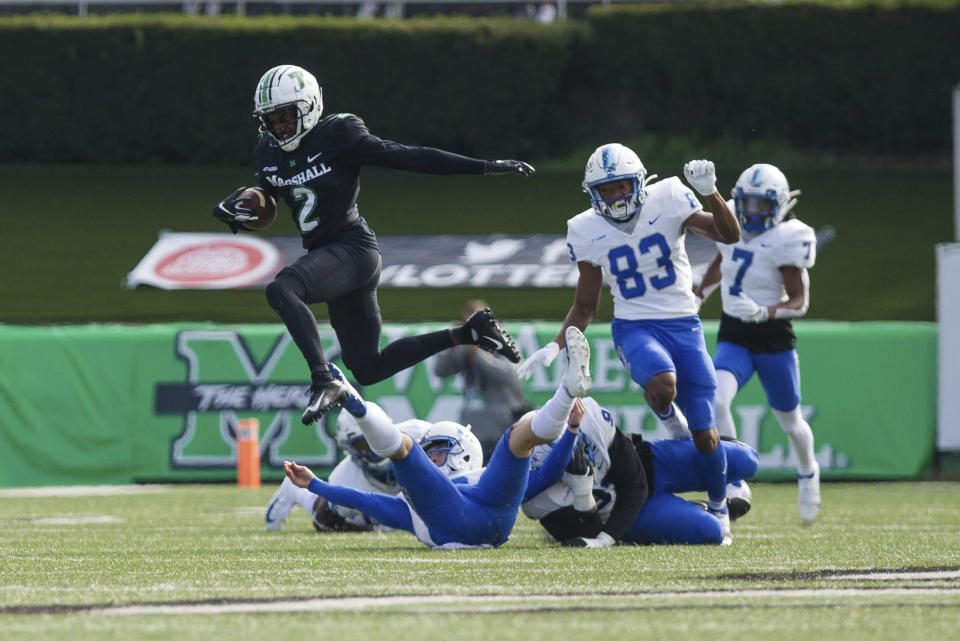 Marshall's Artie Henry (2) leaps over several downed Middle Tennessee defenders on a punt return during an NCAA college football game Saturday, Nov. 14, 2020, in Huntington, W.Va. (Sholten Singer/The Herald-Dispatch via AP)