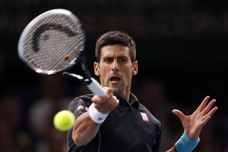 Novak Djokovic of Serbia hits a returns to Pierre-Hugues Herbert of France during their second round men's singles match at the Paris Masters tennis tournament at Bercy stadium in Paris, October 29, 2013. REUTERS/Charles Platiau