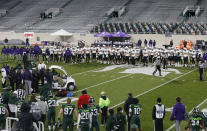 Northwestern players watch at midfield as receiver Berkeley Holman receives medical attention and is carted off the field during the fourth quarter of the team's NCAA college football game against Michigan State, Saturday, Nov. 28, 2020, in East Lansing, Mich. Michigan State won 29-20. (AP Photo/Al Goldis)