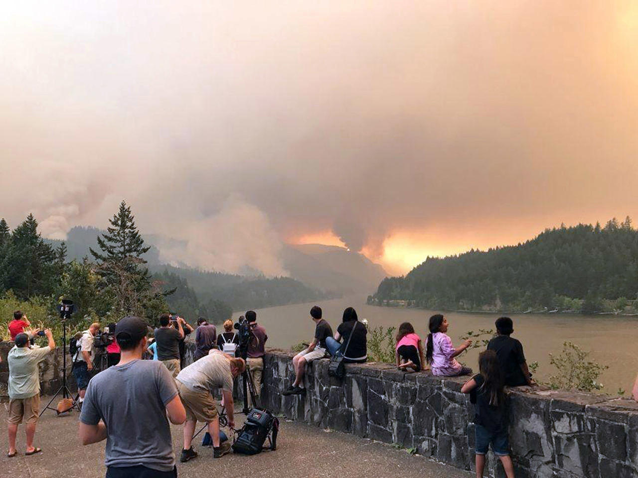 <p>People at a viewpoint overlooking the Columbia River watching the Eagle Creek wildfire burning in the Columbia River Gorge east of Portland, Ore., Sept. 4, 2017. (Inciweb via AP) </p>