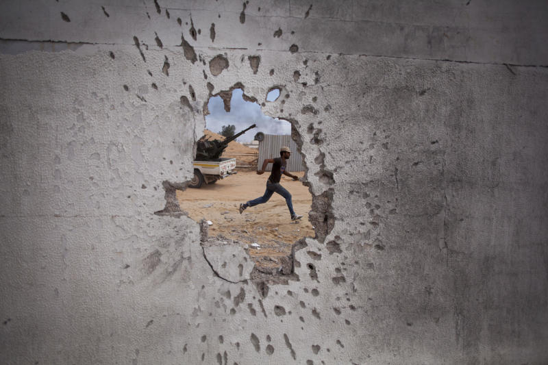 FILE - In this Oct. 7, 2011, file, photo, a Libyan revolutionary fighter runs for cover while attacking pro-Gadhafi forces in Sirte, Libya. Libya has been plunged into chaos again, with forces loyal to a polarizing military commander marching on the capital and trading fire with militias aligned with a weak U.N.-backed government.(AP Photo/Manu Brabo, File)