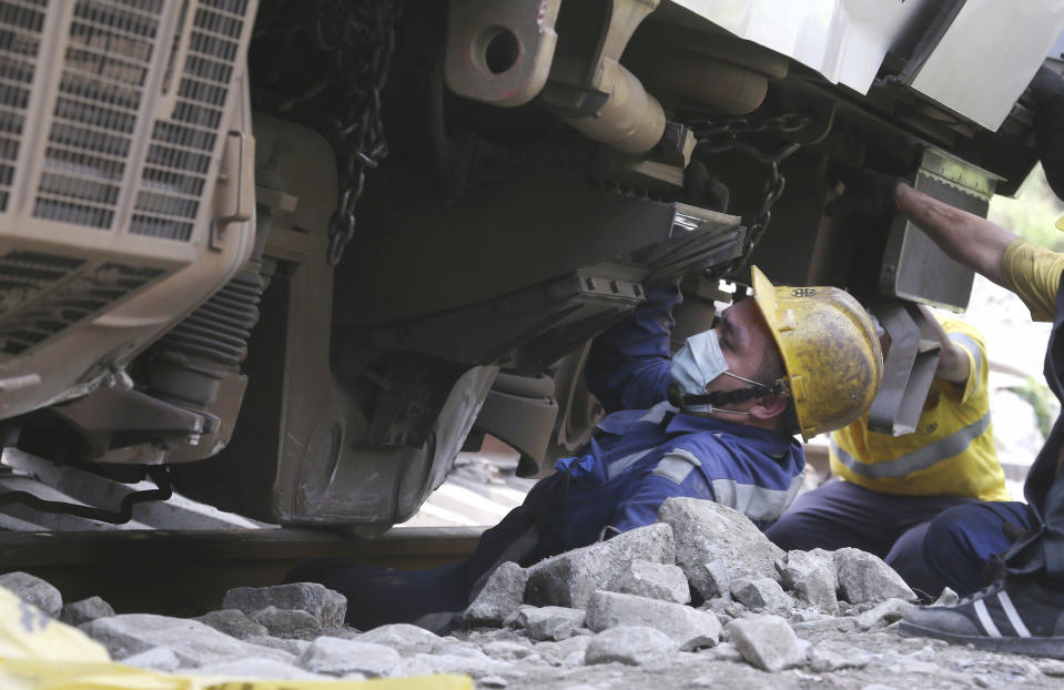 A worker comes out from under the derailed train near Taroko Gorge in Hualien, Taiwan on Saturday, April 3, 2021. The train partially derailed in eastern Taiwan on Friday after colliding with an unmanned vehicle that had rolled down a hill, killing and injuring dozens. Workers began removing some of the train cars and repair work also has begun on the tracks including the tunnel where part of the eight-car train crashed. (AP Photo/Chiang Ying-ying)