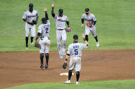 Miami Marlins players engage in a social distant celebration after defeating the Baltimore Orioles 4-0 during a baseball game, Tuesday, Aug. 4, 2020, in Baltimore. (AP Photo/Julio Cortez)