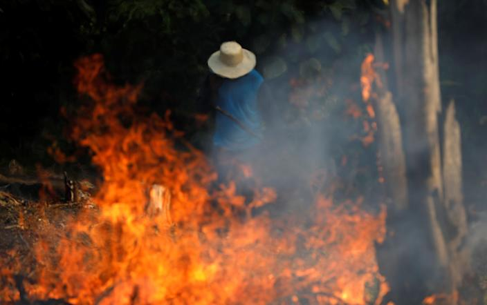 A man works in a burning tract of Amazon jungle in Iranduba, Amazonas state, Brazil, on Aug. 20. (Photo: Bruno Kelly/Reuters)