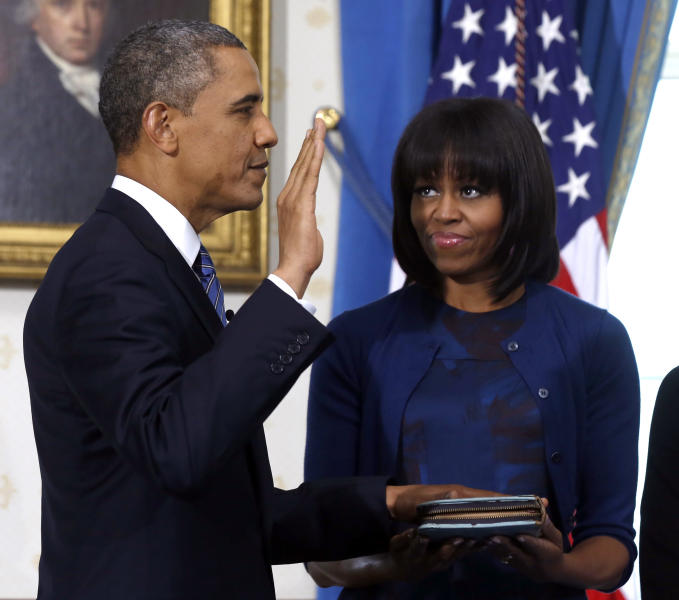 """FILE - This Jan. 20, 2013 file-pool photo shows President Barack Obama officially sworn-in by Chief Justice John Roberts, not pictured, in the Blue Room of the White House in Washington, Sunday, Jan. 20, 2013, as first lady Michelle Obama, holds the Robinson Family Bible. It was a moment for Barack Obama to savor. His second inaugural address over, Obama paused as he strode from the podium last January, turning back for one last glance across the expanse of the National Mall, where a supportive throng stood in the winter chill to witness the launch of his new term. """"I want to take a look, one more time,"""" Obama said quietly. """"I'm not going to see this again.""""There was so much Obama could not _ or did not _ see then, as he opened his second term with a confident call to arms and an expansive liberal agenda. (AP Photo/Larry Downing, File-Pool)"""