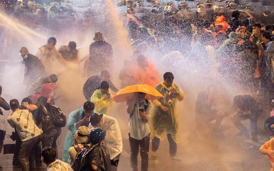 Pro democracy demonstrators face water canons as police try to clear the protest venue in Bangkok - AP