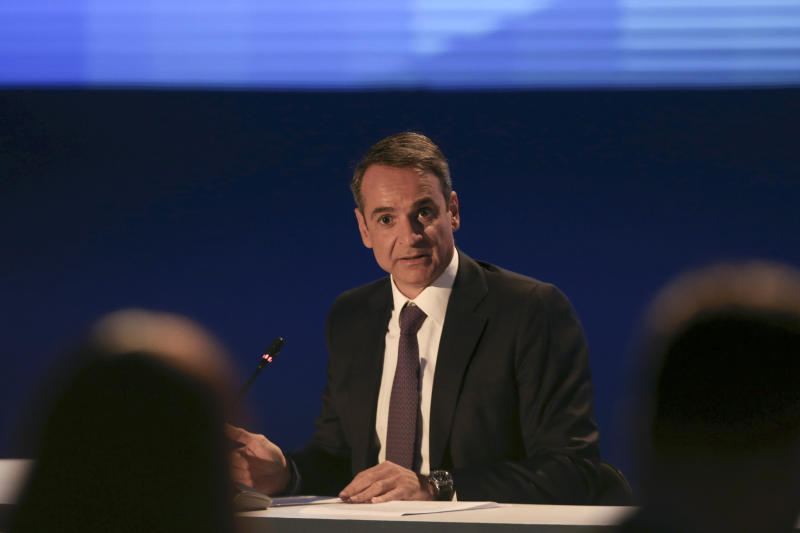 Greece's Prime Minister Kyriakos Mitsotakis waits for a news conference to start during the Thessaloniki International Fair at the northern city of Thessaloniki, Sunday, Sept. 8, 2019. Greece's prime minister said on Saturday that financial reforms such as reducing taxes, fighting bureaucracy and attracting investment must be implemented before the country asks its creditors to agree to lower budget surpluses. (AP Photo/Giannis Papanikos)