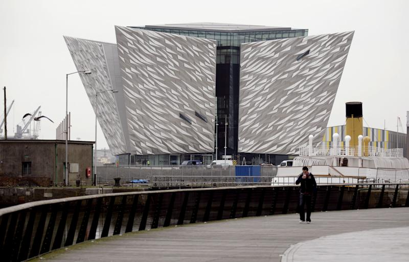 FILE - In this Tuesday March 13, 2012 file photo, a man walks past the new Titanic Belfast Visitor's Center  in Northern Ireland, opening March 31 near the defunct shipyard where the doomed ocean liner was built 100 years ago. Titanic artifacts, models, tours and talks are taking place in many parts of England and North America to mark the centennial of the ship's April 15 sinking.(AP Photo/Peter Morrison, File)
