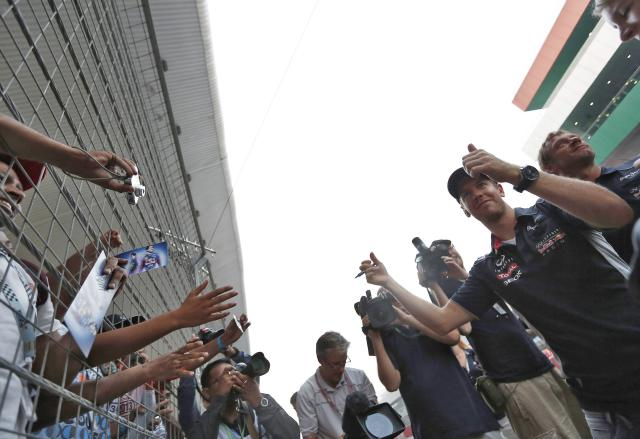 Red Bull Formula One driver Sebastian Vettel (2nd R) of Germany gestures to his fans at the Buddh International Circuit in Greater Noida on the outskirts of New Delhi October 24, 2013. The Indian F1 Grand Prix will take place from October 25-27. REUTERS/Adnan Abidi (INDIA - Tags: SPORT MOTORSPORT F1)