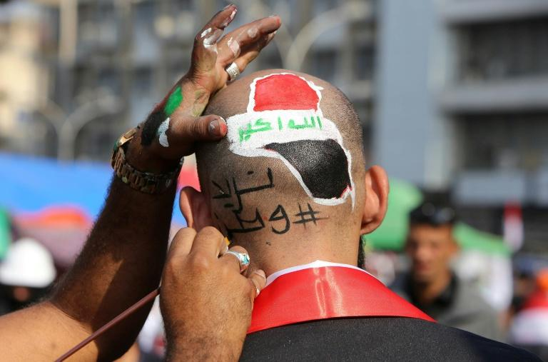 "This Iraqi protester had the slogan ""We need a country"" painted on his head (AFP Photo/SABAH ARAR)"