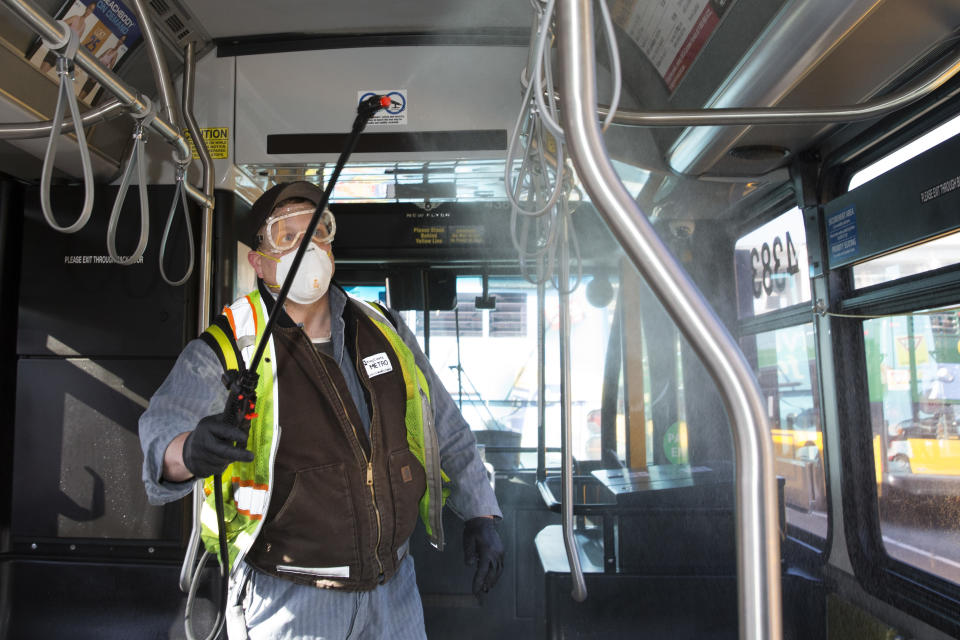 Larry Bowles, an equipment service worker for King County Metro, sprays Virex II 256, a disinfectant, throughout a metro bus at the King County Metro Atlantic/Central operating base in Seattle, Washington.