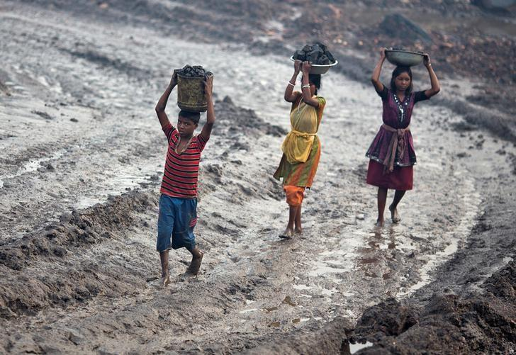 Locals carry coal from an open cast coal field at Dhanbad district in Jharkhand