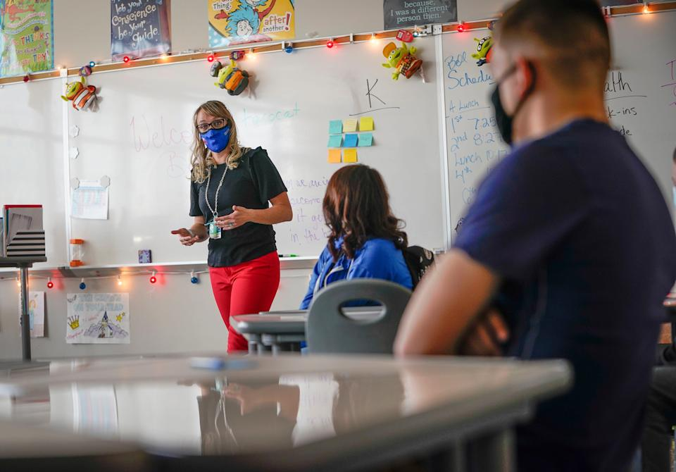 West Mesa High School teacher Stephanie Davy teaches a health class to seven students in person, and other students online, at West Mesa High School in Albuquerque, N.M., on April 6. It was the first week of in-person learning since COVID-19 prompted buildings to close in March 2020.