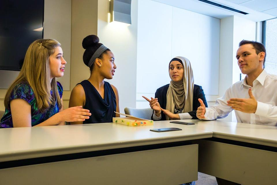 Four people have a discussion while siting around a table.