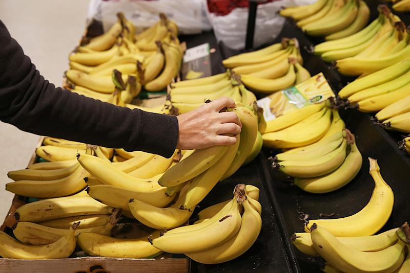 A Woolworths customer reaches for a bunch of bananas on the shelf. Source: Getty