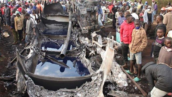 People stand next to a burnt out petrol tanker