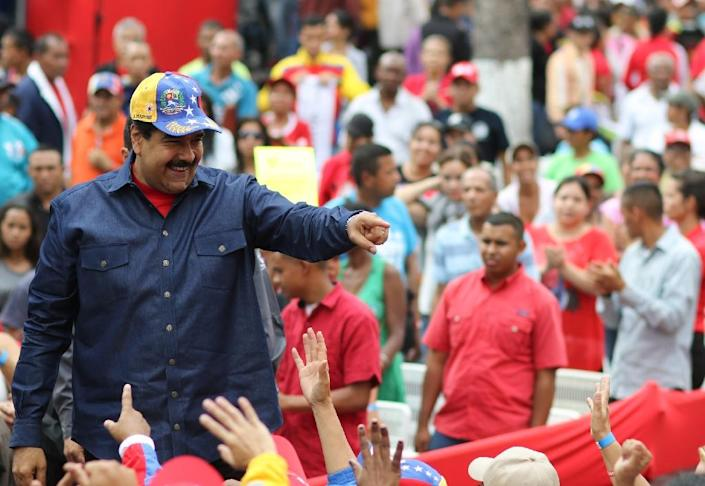 Venezuelan President Nicolas Maduro(L) greets supporters during a rally at the Miraflores presidential palace in Caracas, on May 11, 2016 (AFP Photo/Marcelo Garcia)