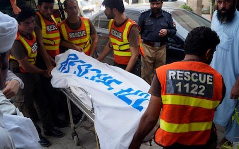 Rescue workers remove the body of Ikramullah Gandapur - Credit: AP