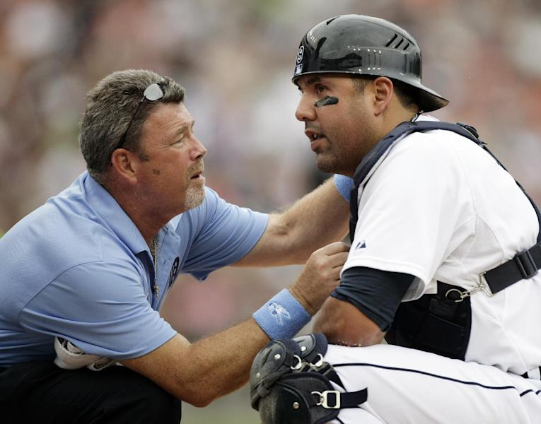 Detroit Tigers catcher Gerald Laird, right, is examined by trainer Kevin Rand after getting hit in the face mask with a ball in the second inning of an interleague baseball game against the Colorado Rockies, Sunday, June 17, 2012, in Detroit. (AP Photo/Duane Burleson)