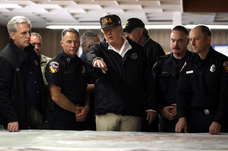 President Donald Trump looks at a map as he visits with first responders and local officials at an operations center responding to the wildfires, Saturday, Nov. 17, 2018, in Chico, Calif. House Majority Leader Kevin McCarty of Calif., is at left. (AP Photo/Evan Vucci)