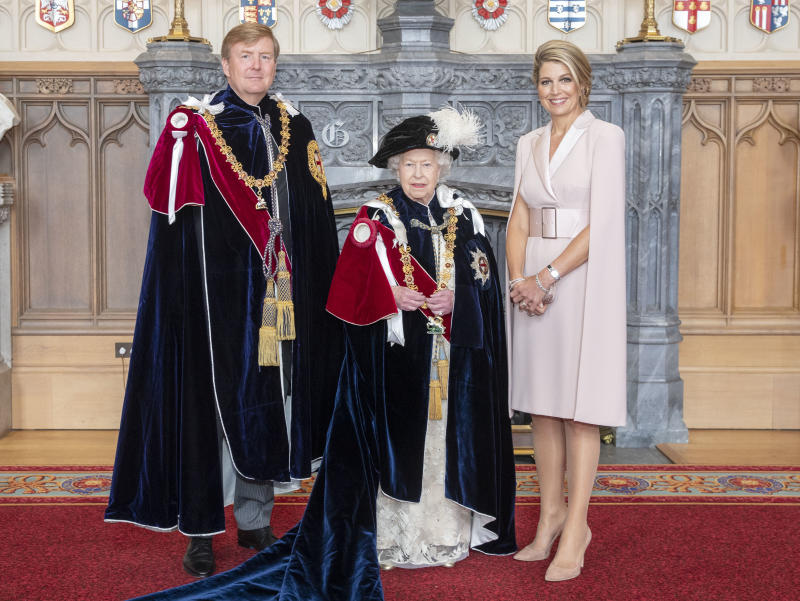 Queen Elizabeth II (centre) with King Willem-Alexander of the Netherlands and his wife, Queen Maxima, in St George's Hall, at Windsor Castle, after the king was invested as a Supernumerary Knight of the Garter, ahead of the Order of the Garter Service at St George's Chapel.