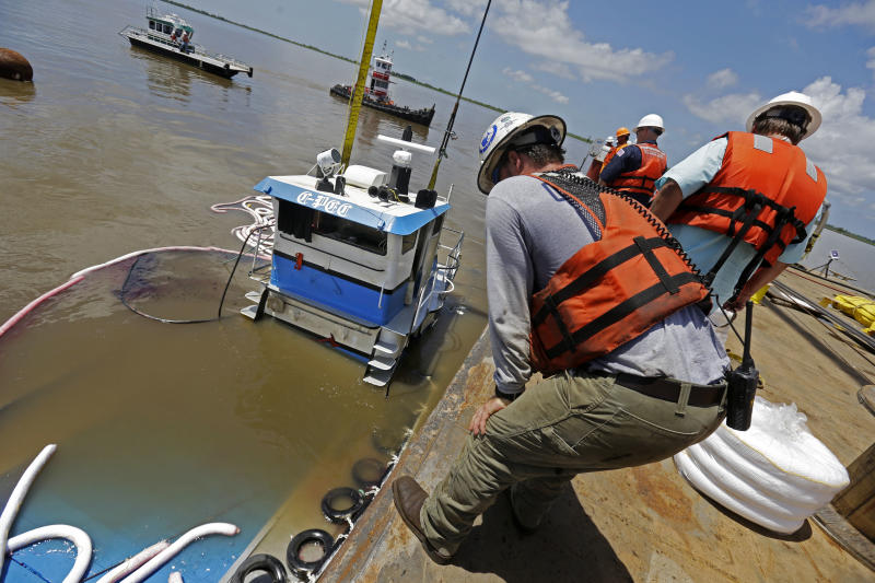 "Workers raise ""C-Pec,"" the 47-foot tugboat which sank Saturday in the middle of the Mississippi River, near Venice, La., Wednesday, July 10, 2013. (AP Photo/Gerald Herbert)"