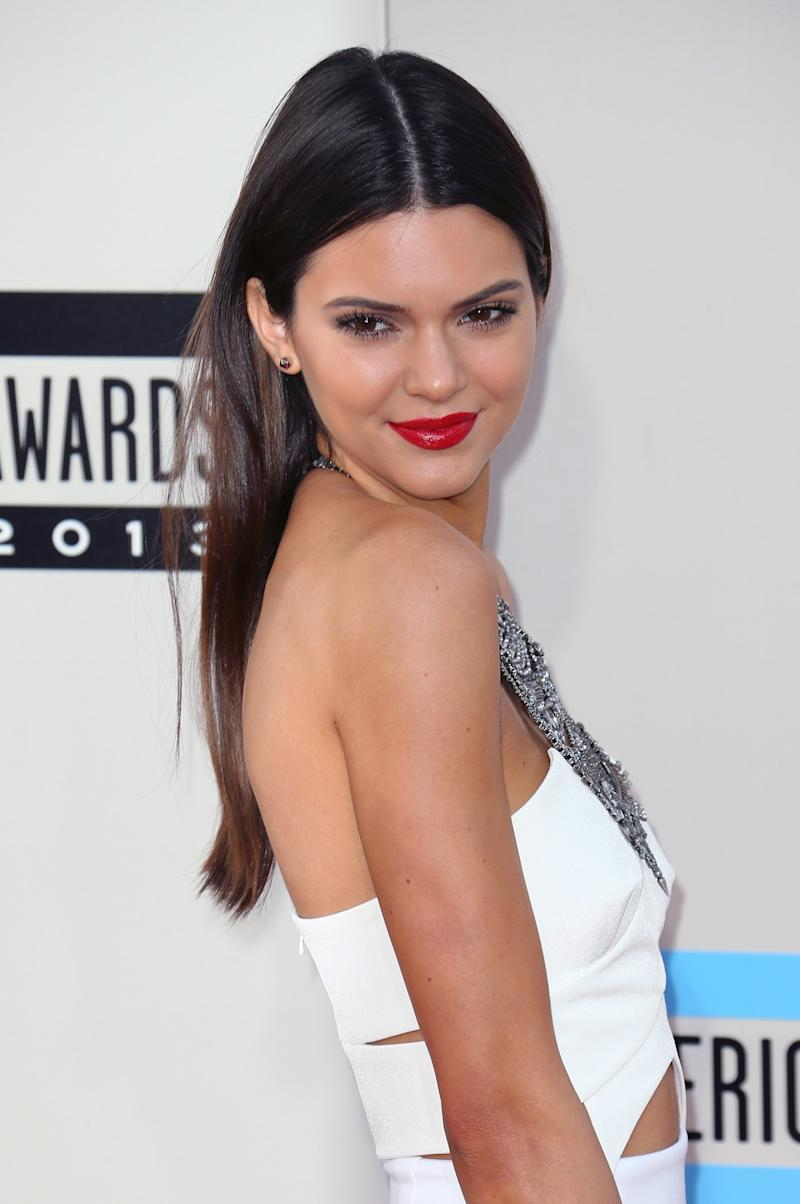 With her modeling career reaching new heights, Jenner grows into her signature look of a sleek middle part and minimal makeup, save for a bold red lip at the American Music Awards in 2013.