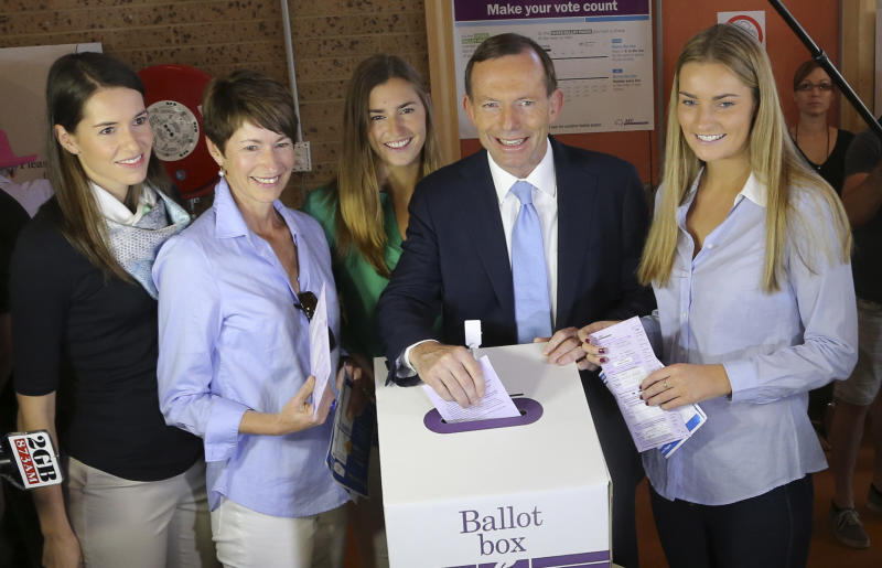 Australia's opposition leader Tony Abbott, second right, and his family from right, Bridget, Frances, wife Margaret and Louise cast their ballots at Freshwater Surf Club in Sydney, Australia, Saturday, Sept. 7, 2013. Australians headed to the polls on Saturday in an election that pits a ruling party marred by infighting and a much-maligned carbon tax against a conservative opposition led by a man who has never been particularly popular and has long been polarizing. (AP Photo/Rob Griffith)