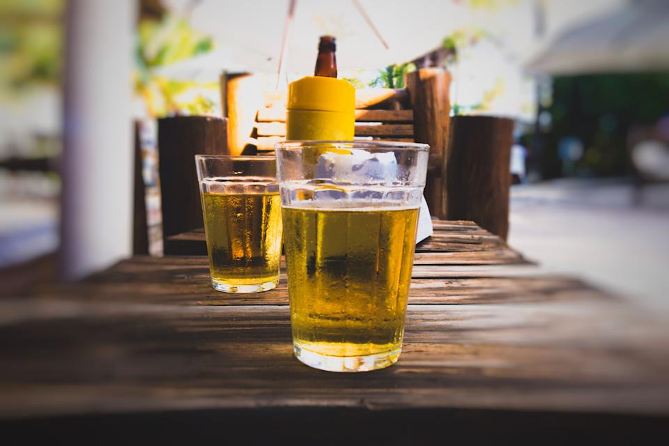 Glass of cold beer on wooden table at bar in summer. Bar on the beach