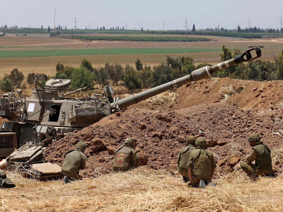 Israeli soldiers take cover at their position near Sderot in southern Israel on the border with the Hamas-controlled Gaza Strip during shellingMenahem Kahana/AFP via Getty Images