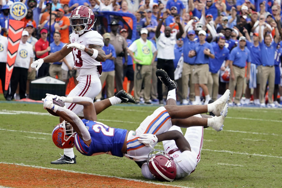 Florida running back Malik Davis, center, stretches the ball over the goal line to score a touchdown on a 26-yard run past Alabama defensive back Malachi Moore, left, and linebacker Chris Braswell, right, during the first half of an NCAA college football game, Saturday, Sept. 18, 2021, in Gainesville, Fla. (AP Photo/John Raoux)