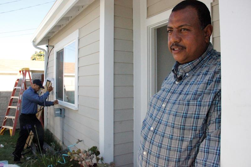 Habitat for Humanity homeowner Girmachew stands in the doorway of his Los Angeles home as a technician from Kahn Air installs a Carrier ductless home comfort system in his home. More than 150 Carrier ductless systems are being installed in Los Angeles as part of a donation of more than 500 systems donation to Habitat for Humanity this year.