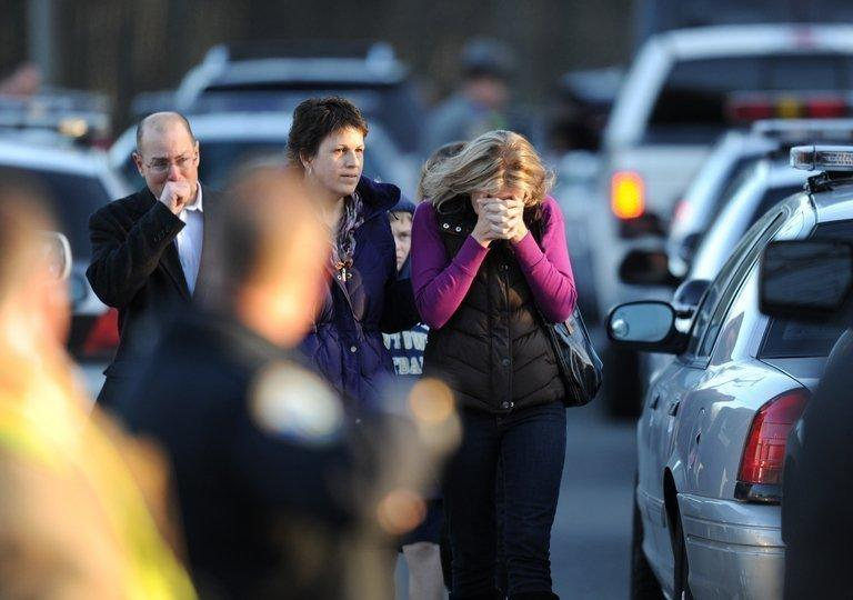Residents grieve at the scene of a school shooting in Newtown, Connecticut, on December 14, 2012