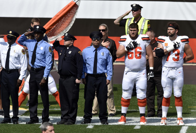Members of the Cleveland police and the Cleveland Browns players stand together during the national anthem. (AP)