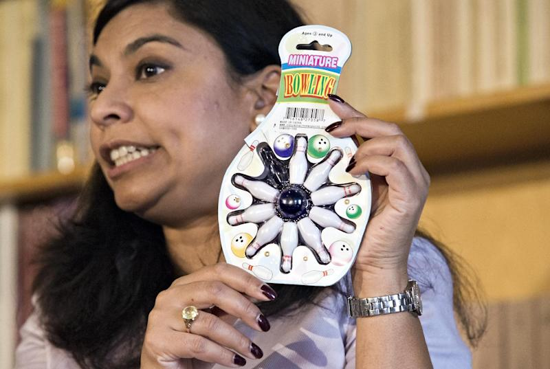 Nasima Hossain, a U.S. Public Interest Research Group (PIRG) advocate, holds a miniature bowling set, that poses a choking hazard, during a PIRG news conference in Washington, Tuesday, Nov. 20, 2012, to release its 27th annual Trouble in Toyland report on hazardous toys.   (AP Photo/J. Scott Applewhite)