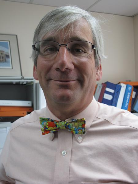 """In this photo taken Thursday, May 31, 2012, in Anchorage, Alaska, State of Alaska labor economist Neal Fried displays his signature bow tie, this one featuring characters from """"The Simpsons."""" A poll by Travel and Leisure magazine says Anchorage has the worst-dressed residents in the nation. Fried says Alaskans would be embarrassed if they had won the category, and says he believes Alaskans are proud to be where they are in the poll. (AP Photo/Mark Thiessen)"""
