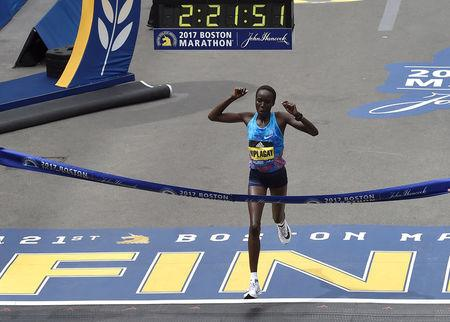 Edna Kiplagat, of Kenya, crosses the finish line to win the women's division of the 121st Boston Marathon in Boston