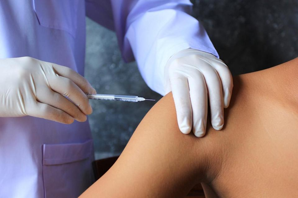 Gloved hands giving an injection into a shoulder