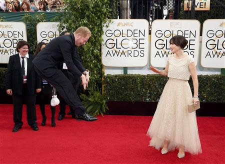 Actress Zooey Deschanel reacts to Jesse Tyler Ferguson jumping at the the 71st annual Golden Globe Awards in Beverly Hills, California January 12, 2014. REUTERS/Danny Moloshok