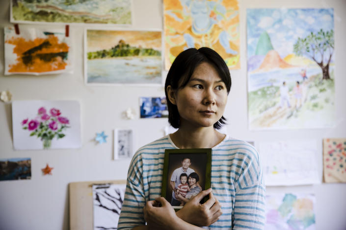 Hua Qu poses for a photograph with a portrait of her family in Princeton, N.J., on May 9. (Photo: Matt Rourke/AP)