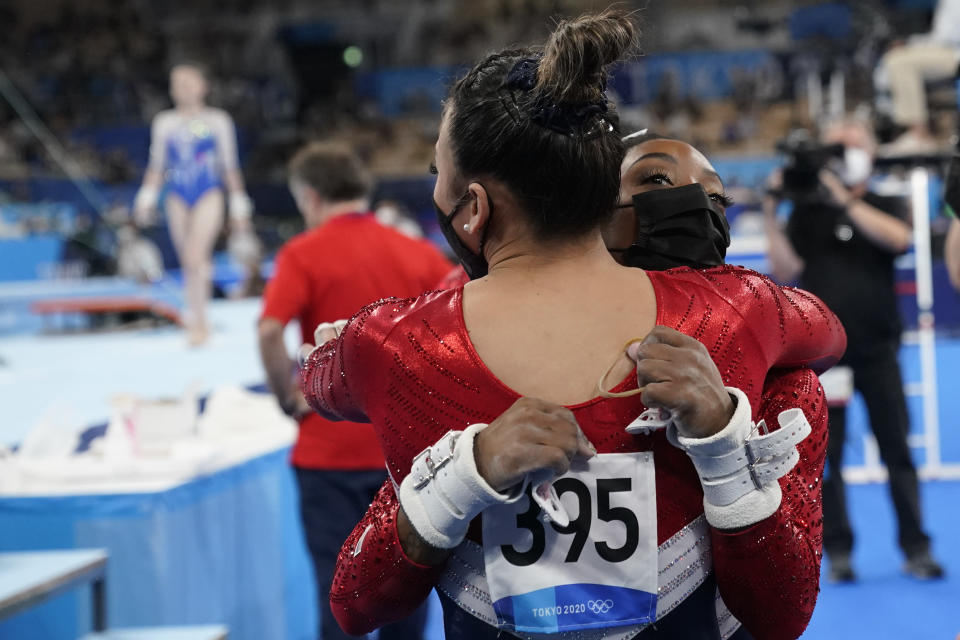 Simone Biles, of United States, right, hugs teammate Sunisa Lee, after pulling out of the women's artistic gymnastic team finals at the 2020 Summer Olympics, Tuesday, July 27, 2021, in Tokyo, Japan. (AP Photo/Gregory Bull)