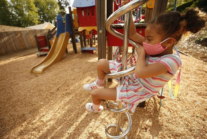 """<span class=""""caption"""">A kindergarten student practices social distancing in the playground of her private school.</span> <span class=""""attribution""""><a class=""""link rapid-noclick-resp"""" href=""""https://www.gettyimages.com/detail/news-photo/kindergarten-student-scarlett-bates-on-the-playground-news-photo/1229580824?adppopup=true"""" rel=""""nofollow noopener"""" target=""""_blank"""" data-ylk=""""slk:Al Seib/Los Angeles Times via Getty Images"""">Al Seib/Los Angeles Times via Getty Images</a></span>"""