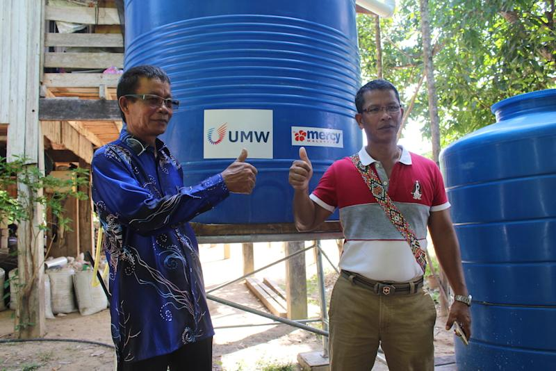 Marius Mokinson (right) and village head Juslee Bokoot with one of the newly installed tanks at a home in Kampung Suang Duyung, Pitas. — Picture by Julia Chan