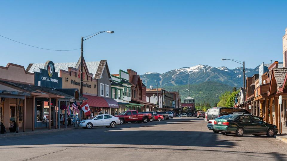 Whitefish, Montana, USA - May 29, 2009 : view of the main street of Whitefish city in Montana with houses, stores, cars.