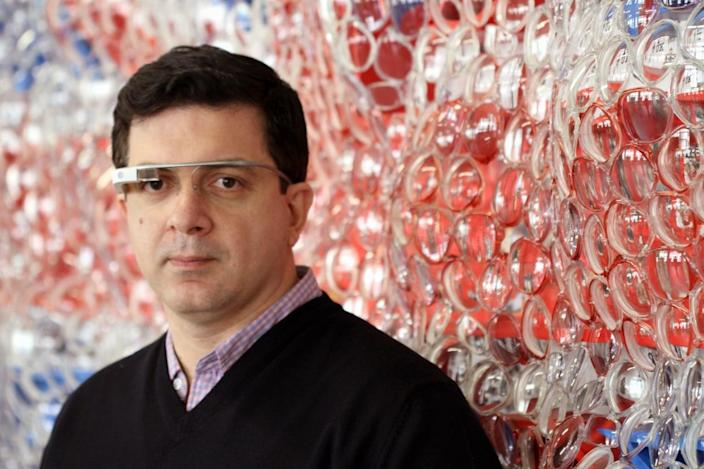 """This undated image provided by Kiwi Arts Group shows David Datuna wearing a Google Glass device, with one of the works from his """"Viewpoint of Billions"""" series behind him. Google Glass devices will be available during Art Basel Miami Beach, Dec. 5-8, for use by the public in interacting with Datuna's works. (AP Photo/Kiwi Arts Group)"""