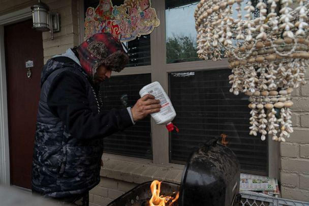PHOTO: Victor Zelaya tries to start a fire on a barbecue grill during power outage caused by the winter storm on Feb. 16, 2021, in Houston. (Go Nakamura/Getty Images)
