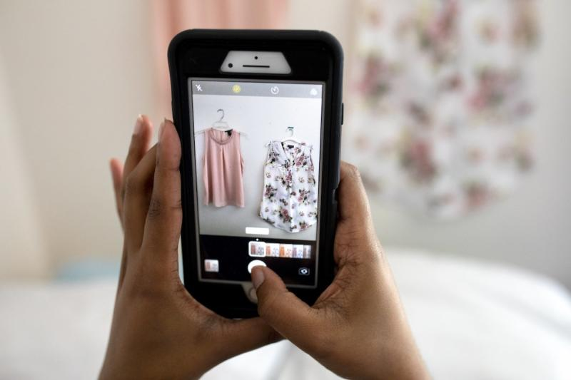 A woman uses her cell phone to photograph clothes she is selling online.