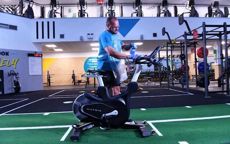 Personnel trainer Paul Joseph cleans down an exercisse bike in preperation for the eventual re-opening of Pure Gym's facility at Park Royal in west London, although group activities may not be allowed at the beginning - Russell Sach