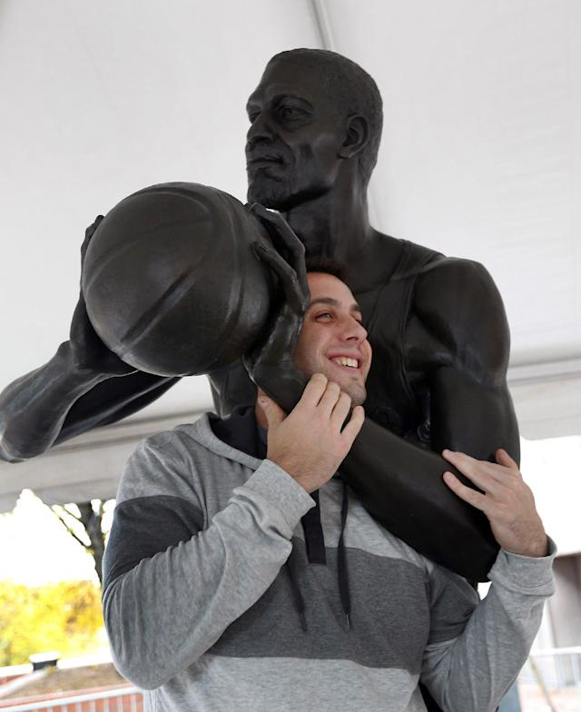 John Tangney, of Worcester, Mass., poses with a newly unveiled statue of former Boston Celtics basketball star Bill Russell at City Hall Plaza in Boston, Friday, Nov. 1, 2013. (AP Photo/Elise Amendola)
